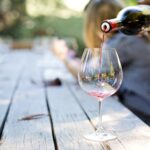 Une main verse du vin dans un verre